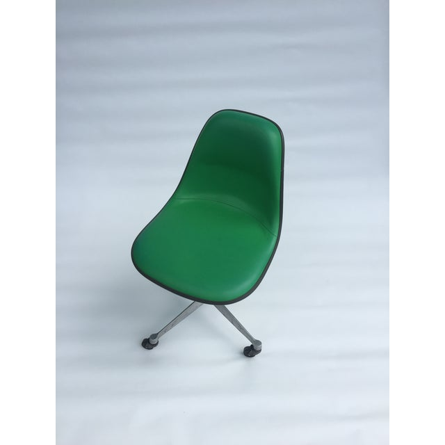 Kelly green fiberglass and vinyl padded Eames shell chair with rare back support on four point rolling office base....