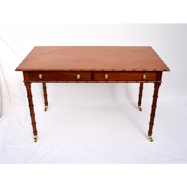 An exceptional Regency Faux bamboo writing desk of solid Mahogany construction on brass casters. Two generously sized...