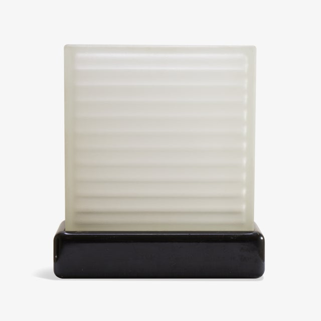 A functional piece of Art-Deco design, elegance and simplicity in one. A large frosted glass block sets inside a black...