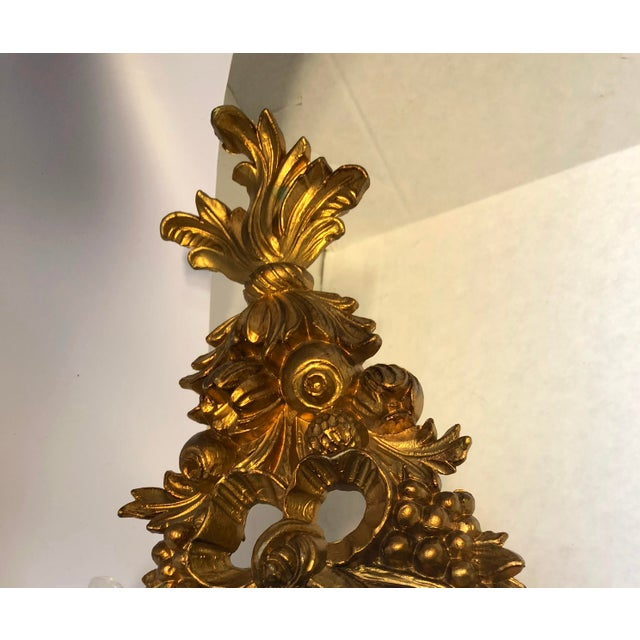 Italian-made mirror from the 1960s, featuring gold-painted flourished carving. It is crafted entirely of moulded resin,...