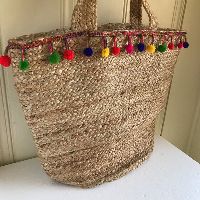 Large Bonjour boho jute basket, market tote or hamper with colorful pompom accents and sturdy handles. Perfect for the...