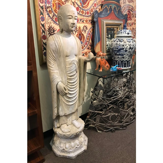Asian carved hardwood and polychromed Buddhist figure holding alter fruit. Standing on lotus base,19th century.