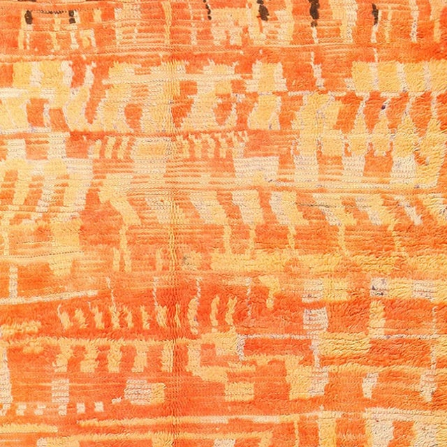 Featuring a vibrant burnt orange color palette, this vintage Moroccan Berber rug uses its the rich tones and hues to...