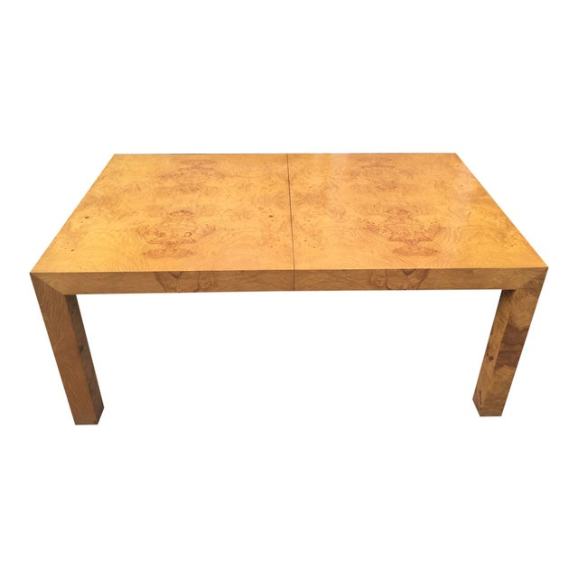 A perfectly-proportioned Parsons table by Milo Baughman, with two extension leaves. Highly figured burled olive wood. A...