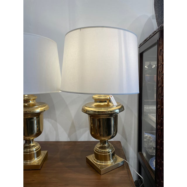 Trophy-like vase shaped table lamps made of brass with warm patina. The material and shape have a strong eye-catching...