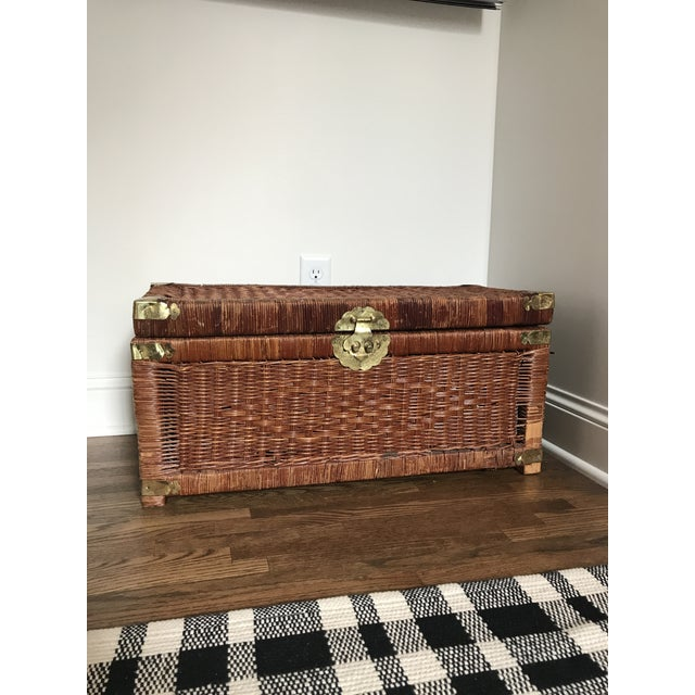 Stained wicker trunk features engraved brass hardware and locking hinge. Decent vintage condition with abrasions, and a...