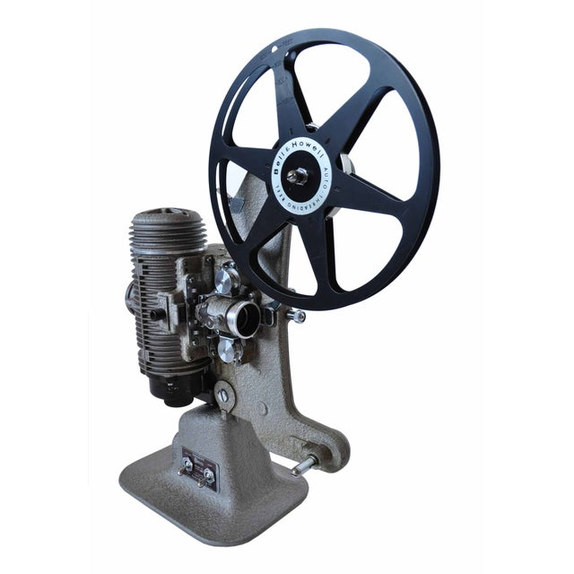 """A Bell & Howell Regent 8mm Home Projector. Includes a durable case that measures 12""""L x 7""""W x 16""""H, a reel and a plug."""