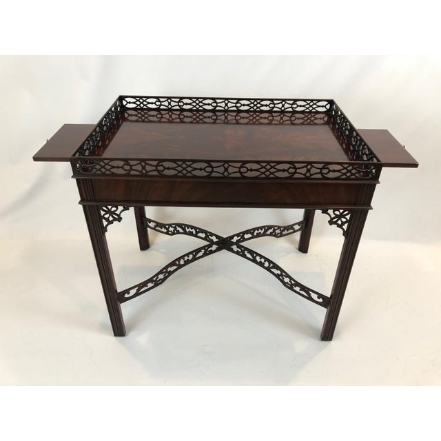 A beautiful Chippendale style rectangular side or tea table having two slides on each end and magnificently crafted wooden...