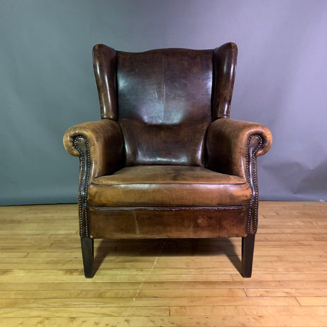 Always classic. Large worn leather wing chair with stitched and squared panels on seat back with tacking work overall....