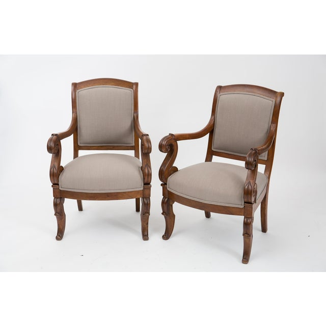 Pair of 19th century French Restauration period armchairs in solid hand-carved walnut with console legs in the front,...