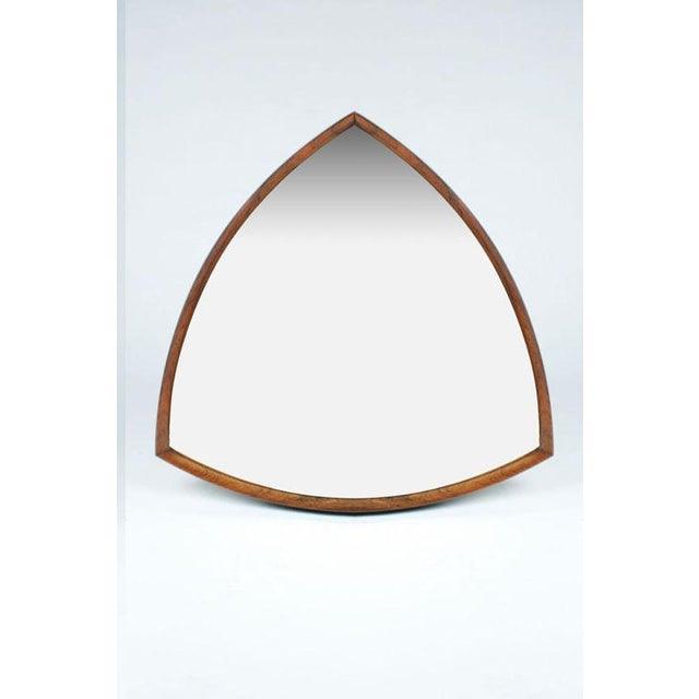 A beautiful mirror with a rosewood frame in a triangular form with bowed sides. Danish, circa 1960.