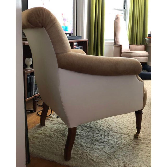 A Salamandre accent chair upholstered in a hair on hide cowhide, with white leather exterior. Brass casters on the front...