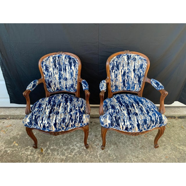 Stunning pair of antique French bergere chairs. Newly upholstered in a velvet. The velvet features blues, white and warm...