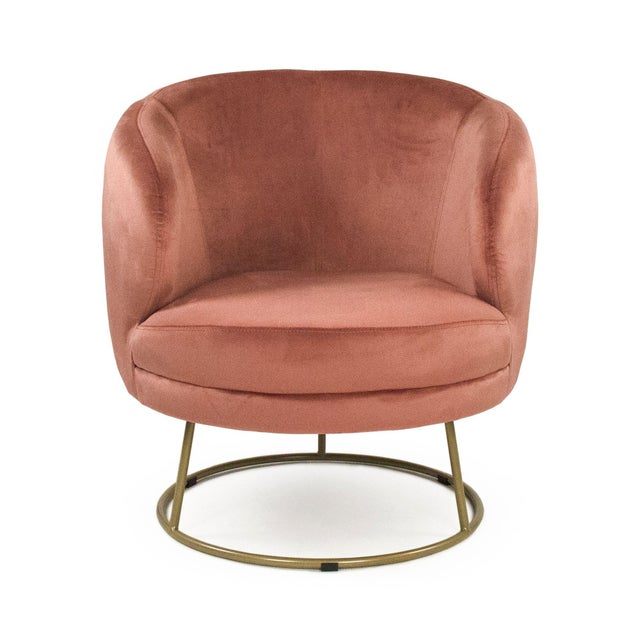 Spacious tub chair upholstered in mauve rose velvet with circular bronze metal frame.