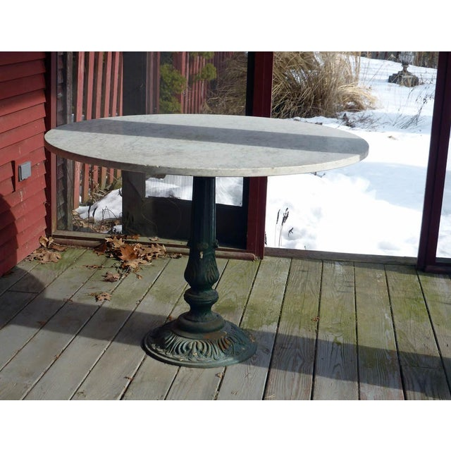 Wonderful 42'' diameter marble topped dining table on a 19th c. cast iron base. Nice wear and patina, easily seats 4....