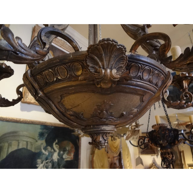 This is a six iron arms with tole bobeches ( US wired ) carved wood chandelier from France . Acanthus leaf design on the...