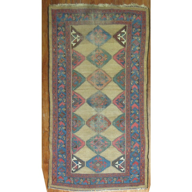 Colorful geometric motif persian rug on a camel background and blue border. Circa 1920.