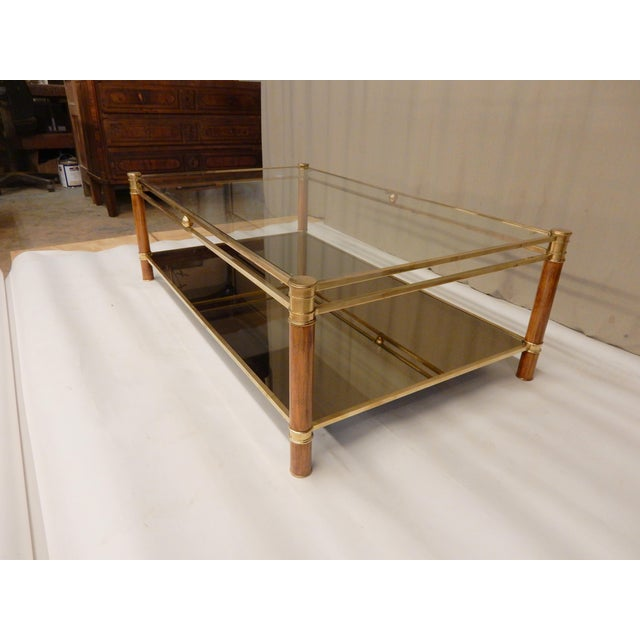 1960's French Mid-Century brass coffee table with clear glass top and mirror shelf. It has very nice walnut columns with...