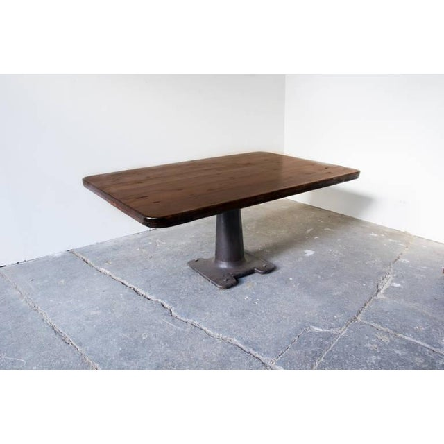 A dining table of solid, reclaimed, wood board construction on an iron pedestal machine base. The pedestal allows for...