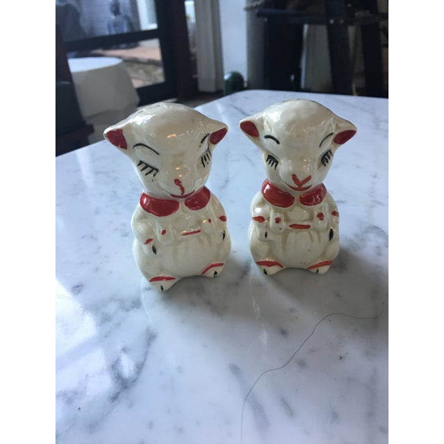 Vintage ceramic salt and pepper shakers that are lambs with red collars. This cuddly pair includes cork plugs and is good...