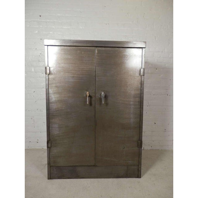Large metal two door cabinet with three point locking system and adjustable shelves. Three shelves are included with...