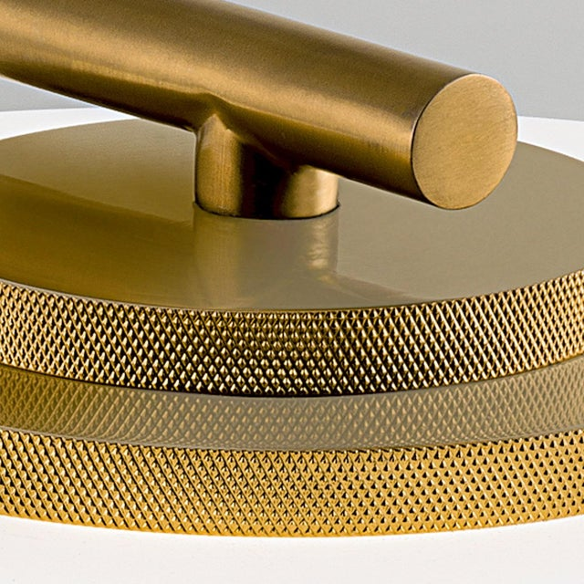 A brushed brass wall light with frosted opal glass. The glass shade is heavily ribbed and secured with metal threads into...
