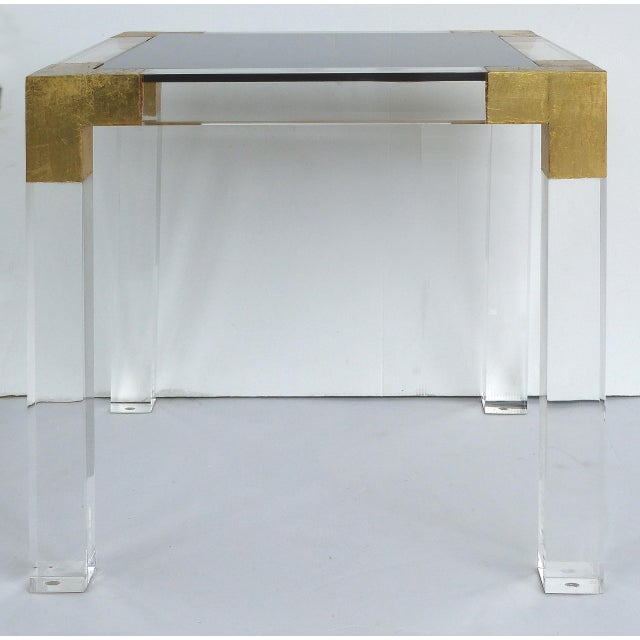 Offered for sale is a custom made side table made of thick lucite having gold leaf accents on the corners and...