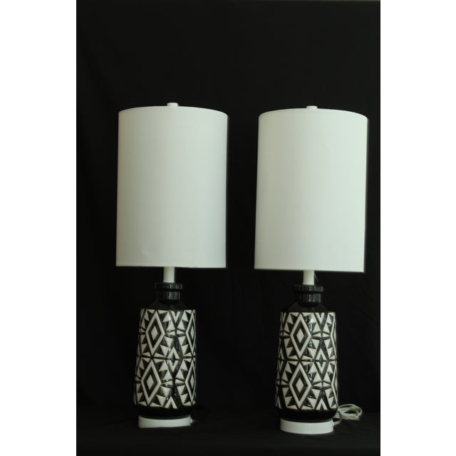 Beautiful pair of black and white ceramic table lamps. Embossed Aztec design makes a interesting texture. These lamps...