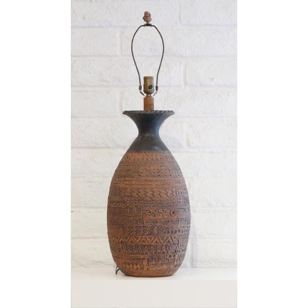 This handsome and interesting table lamp has incised designs in an earthen color. The has a distinct design with circles...