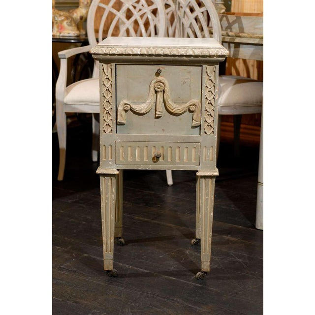 A French late 19th early 20th century richly carved wooden drop-front nightstand table / chest with white marble top, on...