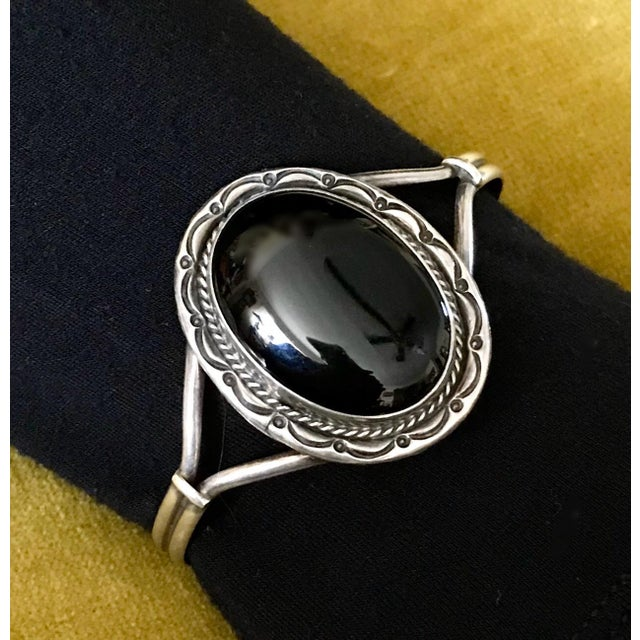 """Circa 1980s sterling silver cuff bracelet bezel set with a large, oval onyx cabochon. The bracelet measures 6.35"""" in..."""