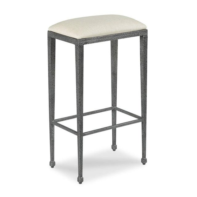 An elegant counter stool with an upholstered seat in repel linen over a metal frame of tapering corner posts that...