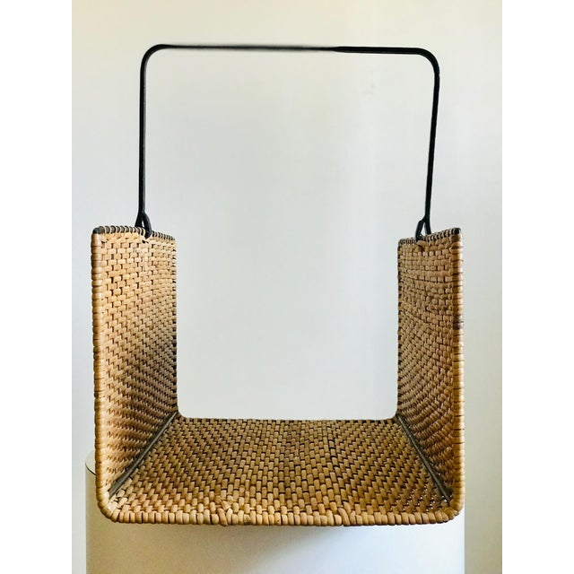 A French style magazine rack framed in forged iron and woven with rattan cane. Elegant simple form with a rich warm patina...