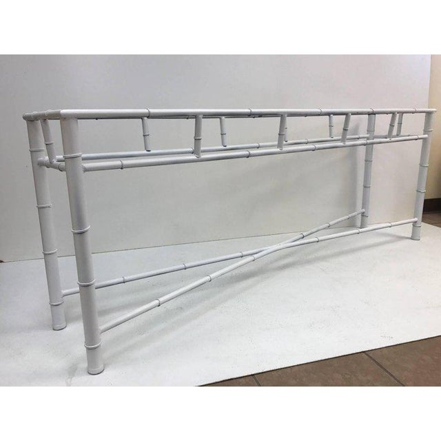 Long faux bamboo console table. Has a white metal painted base.
