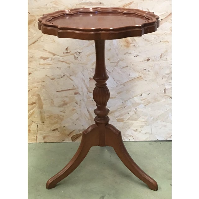About George III oak piecrust wine table with a carved swirl urn form column pedestal on cabriole legs and pad feet....