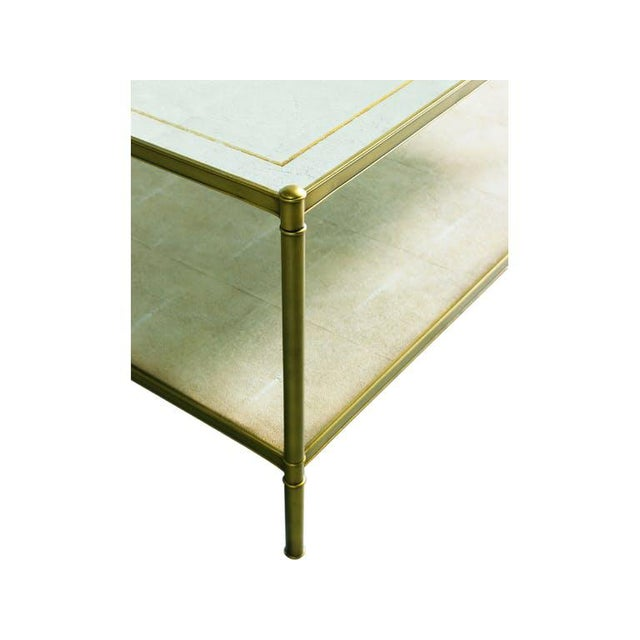 Excellent condition! Square, aged brass cocktail table features and eglomise glass top with aged gold accent stripe and a...