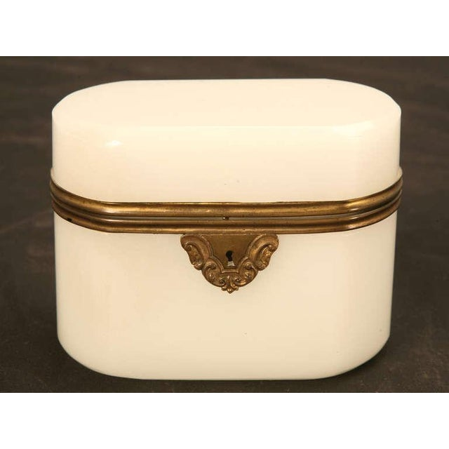Antique opaline glass box with brass trim. All corners are rounded and the top is hinged. Shows wear on bottom and top, as...
