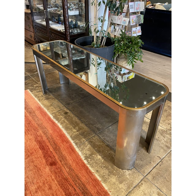 Vintage Mirrored Console Table wrapped with brushed aluminum. This sleek console table will look great in your entryway or...