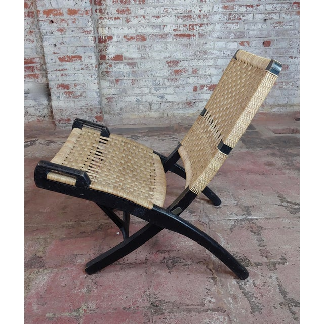 This is a vintage Hans Wegner Style chair . The piece features woven rope and an ebonised frame. The piece also folds.