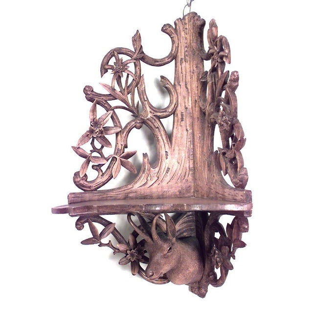 Rustic Continental 'German' stripped corner wall shelf with floral filigree and deer head carving, 19th century.