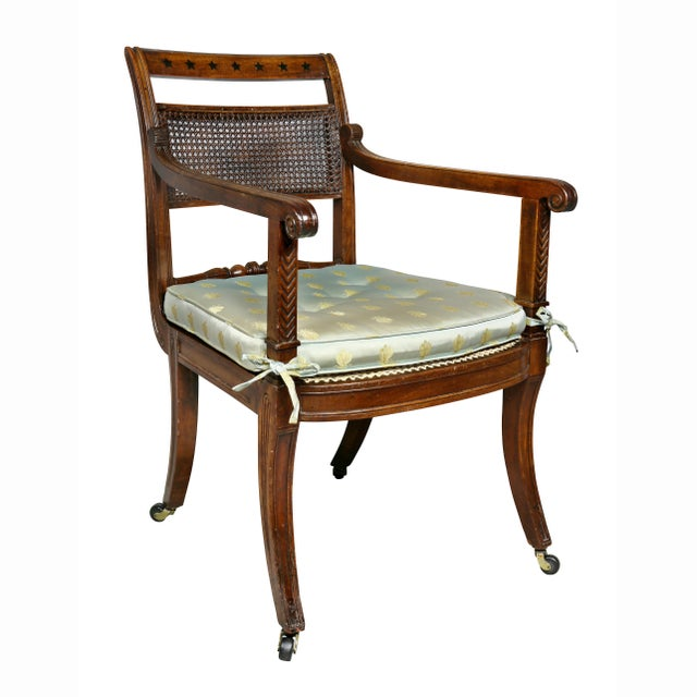 Very elegant side armchair with a tablet crest-rail with star inlay, carved arms, caned back and seat, saber legs....