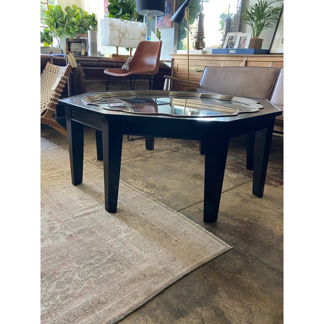 Refurbished Baker octagonal table with aged brass framed inset glass top. Reminiscent of luxe moroccan style, this...
