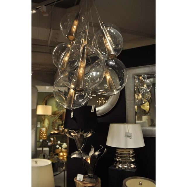 """This adjustable (51""""- 87"""" tall) eight light cluster of the clear glass Caviar spheres ( 3 at 14"""" and 5 at 11 inches)..."""