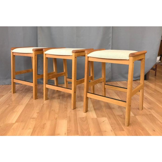 Offered here are a set of three counter stools, a J.L. Møller design for Højbjerg of Denmark. Solid Teak legs and arms,...