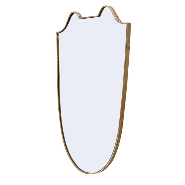 Italian Art Deco period mirror with a brass frame highlighting beautiful curved lines. We love this unique and authentic...