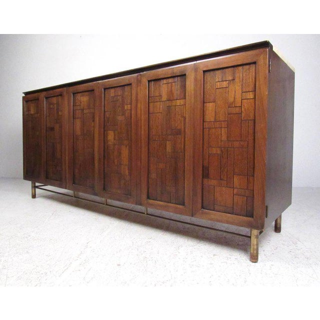 This stylish vintage modern sideboard features sculptural brutalist style cabinet doors, brass legs, and travertine top to...