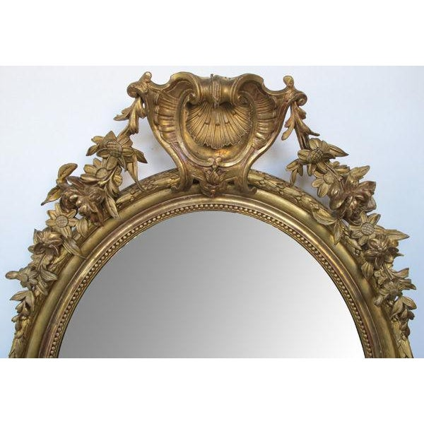 A finely-carved French Napoleon III oval giltwood mirror with shell crest and floral garland; surmounted by a bold shell...