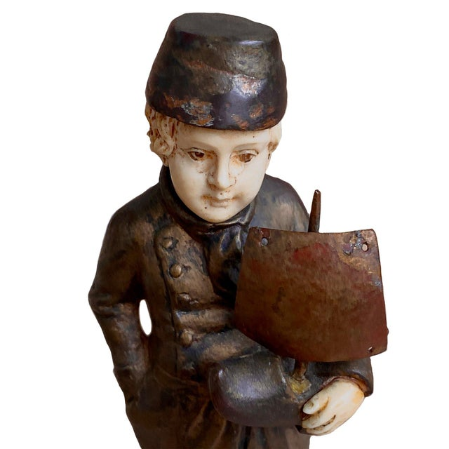 A fine late 19th or early 20th century bronze figure of a boy holding a wooden shoe boat with a sail. It has a rich brown...