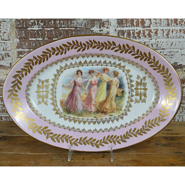 A late 19th century Continental oval porcelain portrait platter featuring a central transfer with four maidens dancing in...