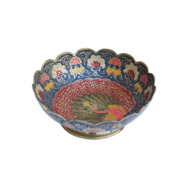 An ornately engraved Moroccan brass bowl. At the center is a red and gold peacock surrounded by paisley petals and floral...